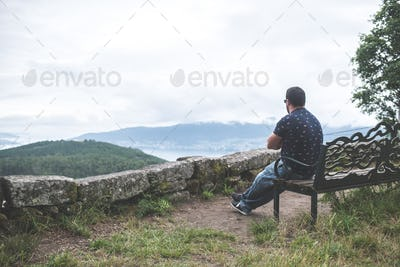 Man sitting on a bench alone, contemplating the landscape