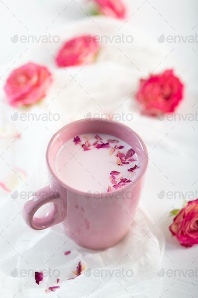 Moon milk prepares with pink rose flower. Trendy relaxing bedtime drink form Ayurvedic traditions