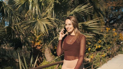 Pretty cheerful blond girl having conversation on the phone outdoor