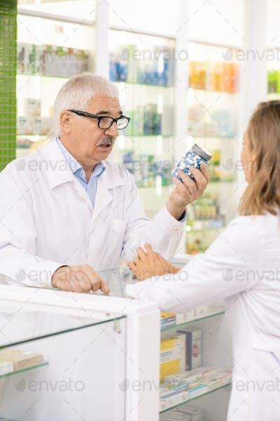 Senior owner of contemporary drugstore showing his subordinate jar with pills