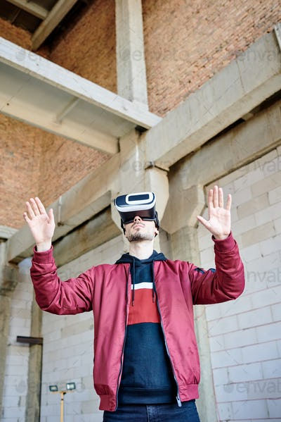 Young man in casualwear and vr headset standing by large virtual display