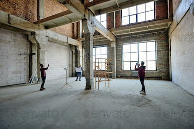 Two young contractors photographing unfinished structure inside building