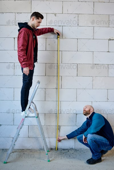 Young builder standing on stepladder and holding measuring tape by brick wall