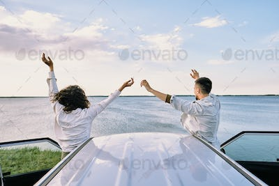 Rear view of young cheerful couple standing close to their car with open doors