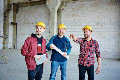 Happy young engineer in hardhat pointing at one of walls of unfinished building