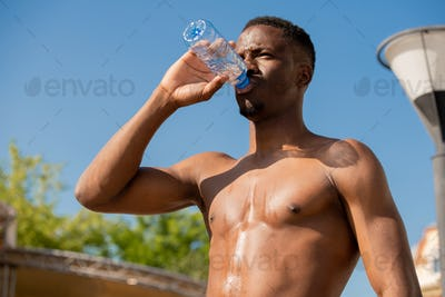 Young shirtless thirsty sportsman drinking water from bottle at break