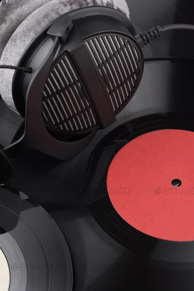Headphones on the heap of different vinyl records.