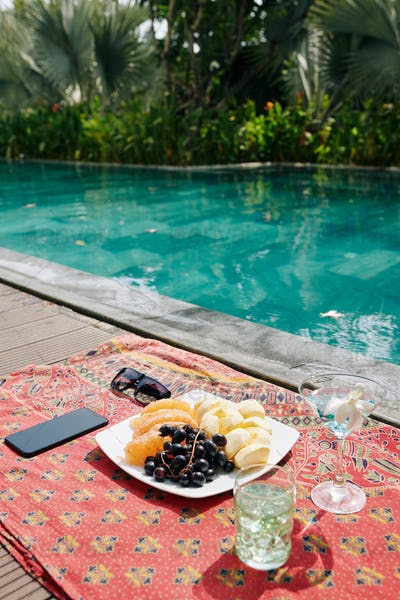 Fruits and cocktails on pool edge