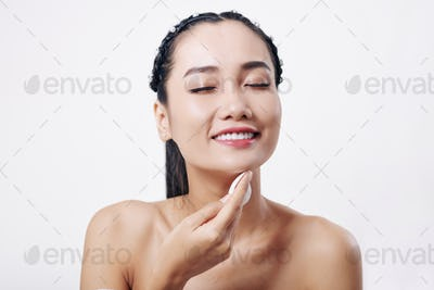 Woman wiping face with cotton pad
