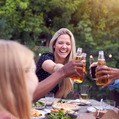Friends Making Toast With Alcohol In Garden At Home Enjoying Summer Garden Party