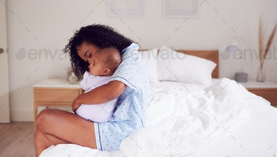 Loving African American Mother Wearing Pyjamas Cuddling Baby Daughter In Bedroom At Home
