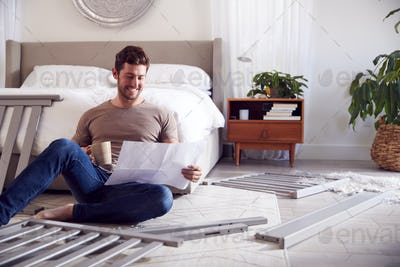 Father To Be Looking At Instructions For Self Assembly Baby Cot In Bedroom