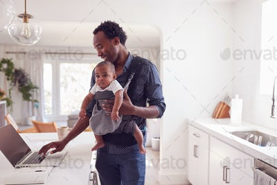Father With Baby Daughter In Sling Multi-tasking Working From Home On Laptop