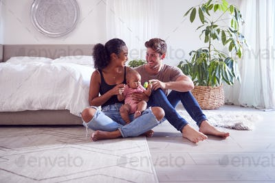 Loving Parents Playing With Baby Daughter Sitting On Floor In Bedroom