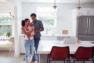Family With Baby Daughter In Kitchen Using Laptop On Counter