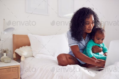 Mother Wearing Pyjamas With Baby Daughter In Bedroom Working From Home On Laptop