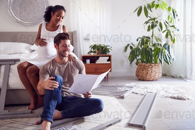 Couple With Pregnant Woman Putting Together Self Assembly Baby Cot In Bedroom