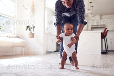 Father Encouraging Smiling Baby Daughter To Take First Steps And Walk At Home