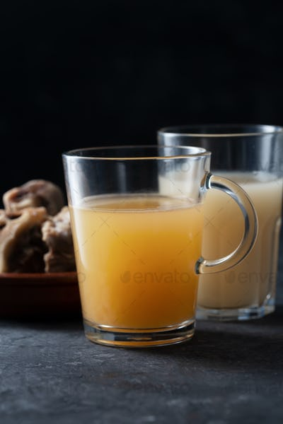 Two types of Homemade Beef Bone Broth in Glasses on a black background