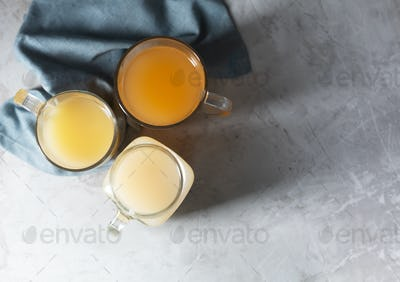 Homemade Beef Bone Broth in Glasses on a gray concrete background, top view with copy space