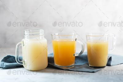 Three types of Homemade Beef Bone Broth in Glasses on a gray background