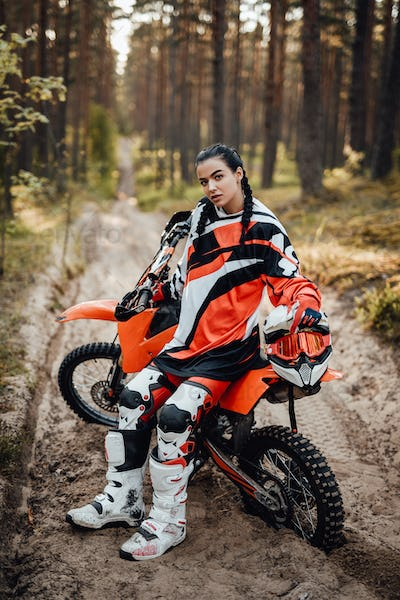 Beautiful female racer sitting on her motocross bike on a trail of sand in the woods