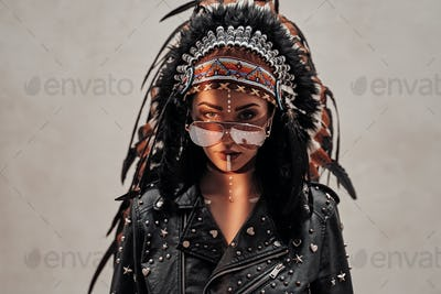 Daring young woman with aztec headdress, tribal make-up, and leather jacket posing in a studio