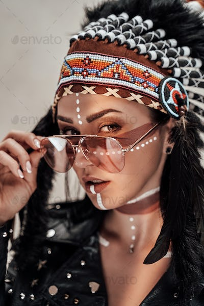Close-up photo of a stylish girl with native American tribal make-up and biker clothes