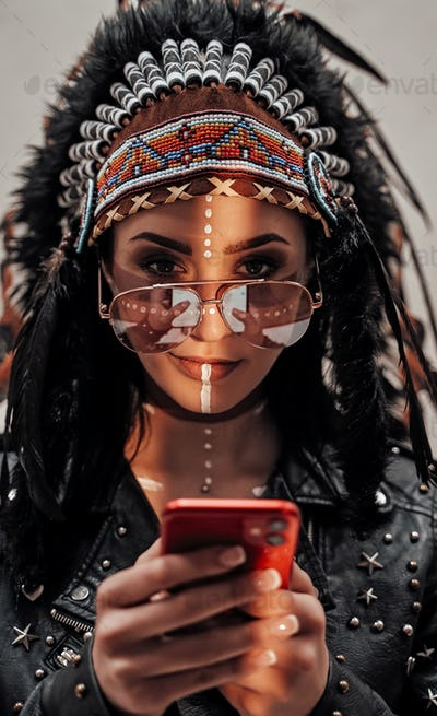 Attractive woman looking on smartphone, wearing tribal headdress and oriental make-up