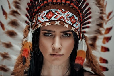 Attractive female looking disappointed and wearing mayan headdress, close-up
