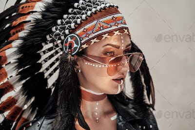 Attractive woman posing in studio and wearing tribal headdress and oriental make-up
