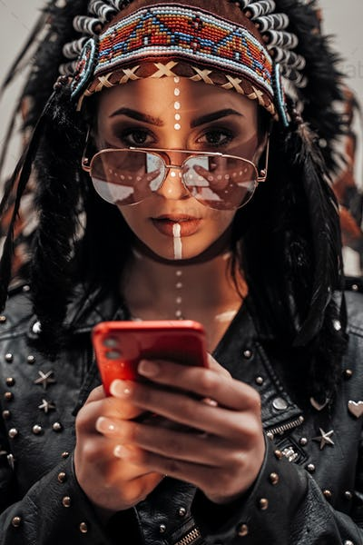 Portrait of a stylish girl with native American tribal make-up and biker clothes with a smartphone