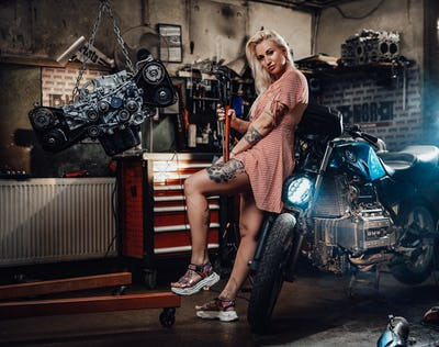 Beautiful blonde girl with tattooed body wearing pink dress posing in garage or workshop