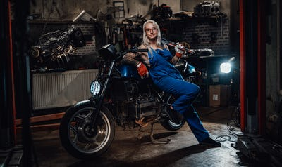Female tattooed mechanic in work overalls hold a big wrench and posing for a camera in garage