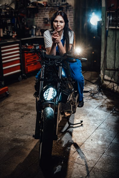Beautiful brunette biker or mechanic relaxing smoking a cigarette in garage or workshop