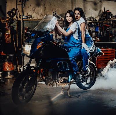 Two female mechanic sitting on sportbike in authentic workshop garage