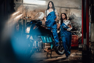 Two brunette women in blue overalls posing next to a sportbike in authentic workshop garage