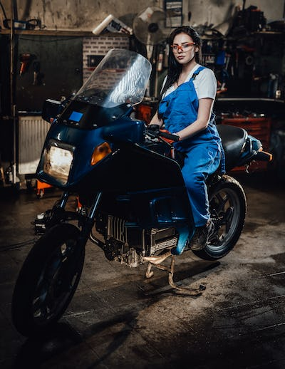 Young brunette female mechanic in blue overalls sitting on sportbike in garage or workshop