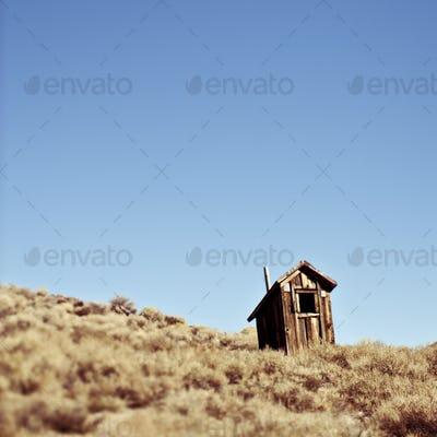 Dilapidated Outhouse on Hillside