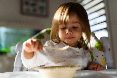Two years old eats brakefast by herself with a spoon.