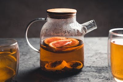 Citrus tea in a transparent teapot. On a gray stone texture background. Healthy drink