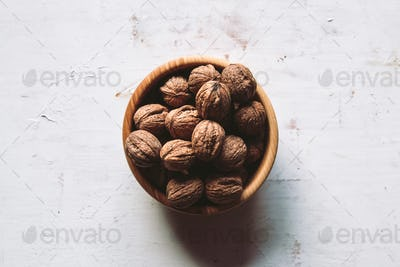 Walnut kernels in a wooden bowl and whole walnuts on a table. Walnuts