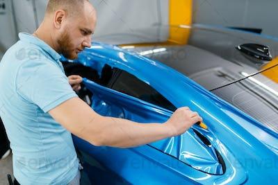 Car wrapping, mechanic cuts vinyl foil or film