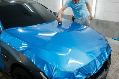 Car wrapping, man with squeegee installs film