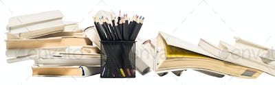 Colored pencils in a pencil pot and stacks of books. Isolate