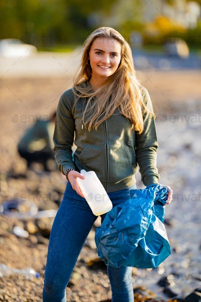 Smiling female volunteer holding bottle and garbage bag at beach