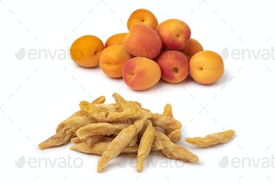 Heap of dried pitted sweet orange apricots and fresh apricots in the background