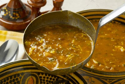 Serving Moroccan harira soup close up