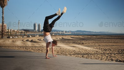 Young handsome sporty man standing on hands during workout on beach
