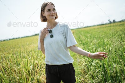 a woman poses in the middle of a rice field